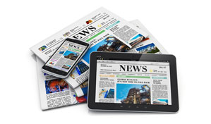 stack of newspapers and devices with news